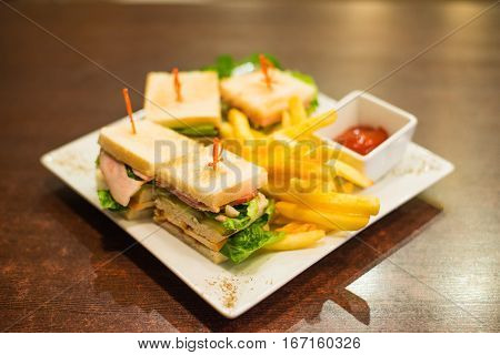 Mini sandwiches with fries and sauce on a white plate