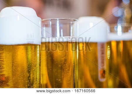Foamy beer in glasses with bubbles on bar stand