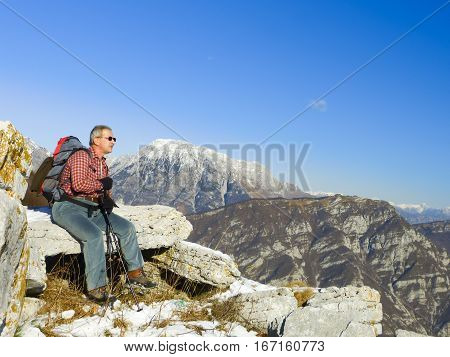 Man of about 60 years resting after rising on the mountain.