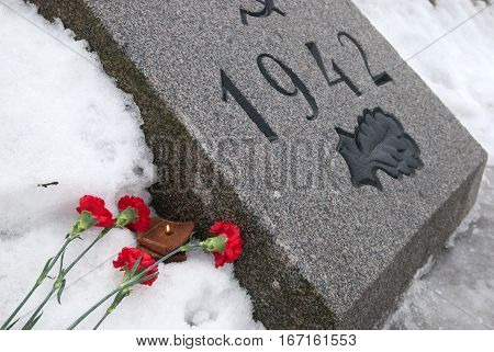 SAINT-PETERSBURG, RUSSIA, JANUARY 28, 2017: Red flowers in the snow and a slice of bread with candle on one of the mass graves on Piskaryovskoye Memorial Cemetery