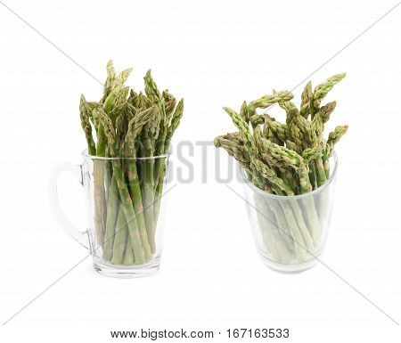Glass filled with the multiple cultivated green asparagus spears isolated over the white background, set of two different foreshortenings