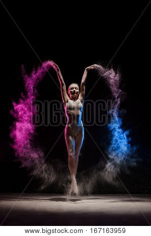 Graceful woman dancing in cloud of pink and blue dust studio shot