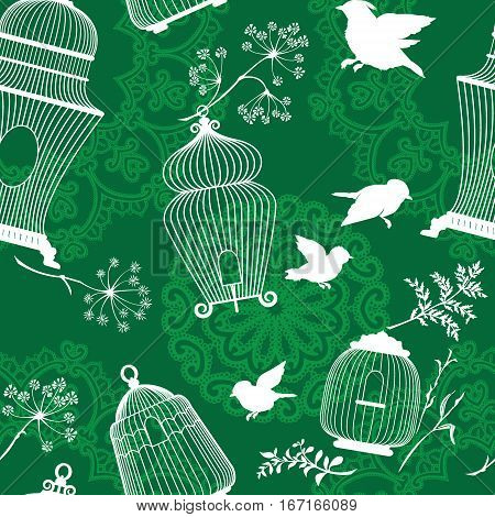 Seamless pattern with decorative white Silhouettes of bird cage flying birds plants on green background with mandala ornaments.