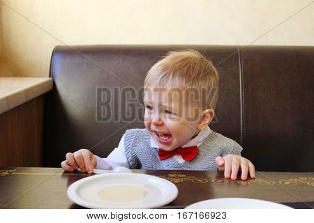 Upset and crying little boy screaming while sitting at the table.