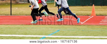 group of girls runing together on a red track during winter track and field practice