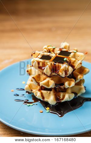 Homemade waffles with chocolate on blue plate
