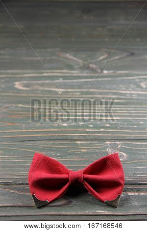 Red bow tie on a wooden background