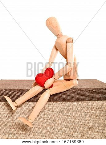 The sad person holds heart in hand. The doll a wooden dummy sits holds in hand heart from red fabric. The pose of the person expresses grief