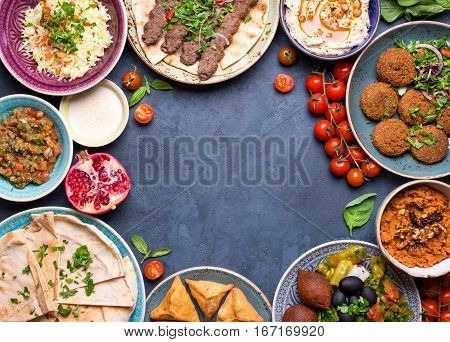 Middle eastern or arabic dishes and assorted meze on concrete rustic background. Meat kebab falafel baba ghanoush hummus sambusak rice tahini kibbeh pita. Halal food. Space for text. Top view