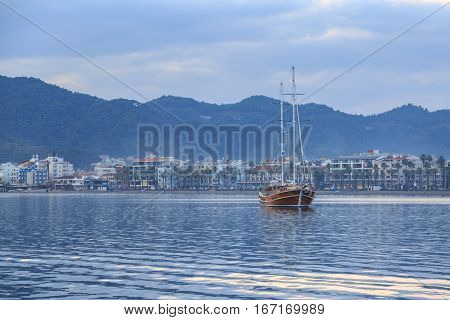Vintage ship with marmaris city background and beach.