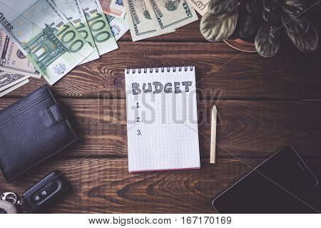 Budget planing concept. Notepad with word Budget, mobile phone, cup of coffee, pouch and money on wooden background. Vintage toned picture. Top view