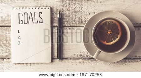 Goals concept. Notebook with goals list, cup of tea on wooden table. Motivation and strategy concept. Top view. Retro toned image.