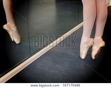 Legs of young ballerina on pointe in a ballet dancing studio with a reflection in the mirror with a vignette and space for text.