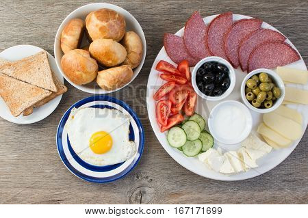 Traditional Turkish breakfast platter on the grey wooden table top view: egg toasts pogaca pasties vegetables cheeses olives and halal turkey salami selective focus; copy space for text
