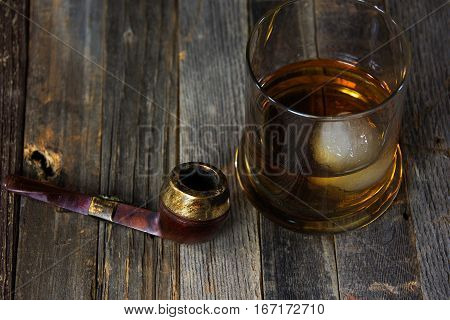 round ice cube in whiskey drink with vintage pipe on rustic wood
