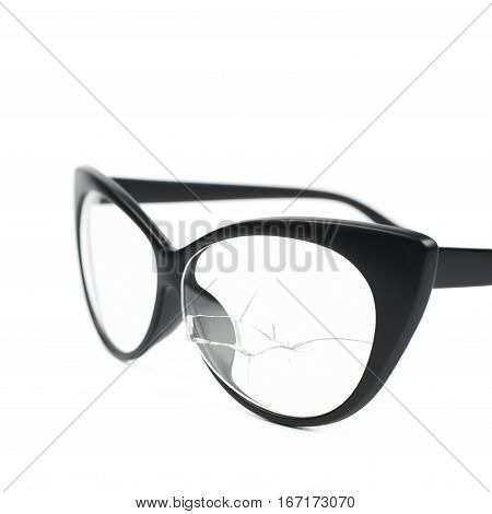Pair of black plastic sight glasses with the broken lens glass, close-up crop composition isolated over the white background