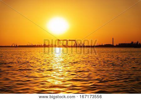 Orange sunset and the river. Shipyard on the horizon