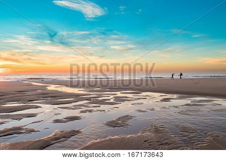 A father and teenager son playing racket in the beach during a winter evening right before sunset