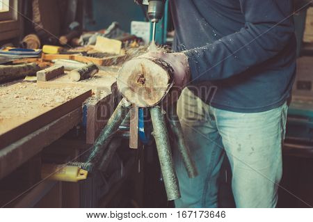 Dark phone photography of the man in old clothes making wooden reindeers from the logs in the shed selective focus