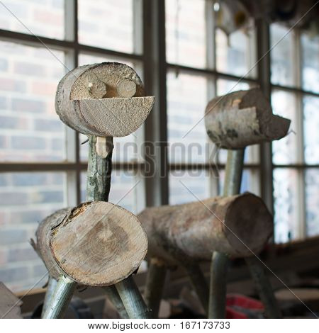 Making wooden reindeers from the logs in the shed selective focus square
