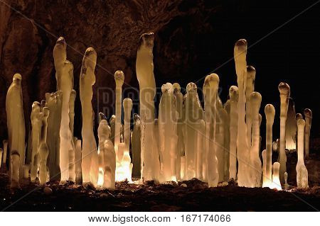 Winter icicles iluminated with battery and candles. Frozen cave in Slovakia. Stalactite and stalagmite. Exploration depths of the earth.