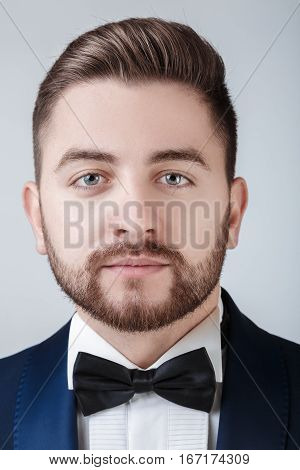 portrait of handsome young man in tuxedo and bow tie looking at camera. Fashionable and festive clothing. emcee on grey background