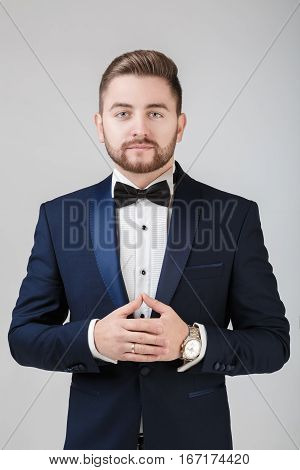 Handsome young man in tuxedo and bow tie looking at camera. Fashionable and festive clothing. emcee on grey background