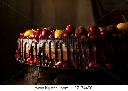 Triple chocolate cake decorated with pomegranate, cranberries and small apples