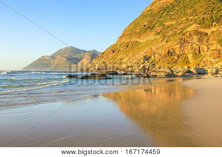 Beautiful Noordhoek Beach, 8 km of sandy beach from Chapmans Peak Drive to Kommetjie, in Table Mountain National Park, South Africa at sunset. Noordhoek beach is popular for horse riding and surfing.