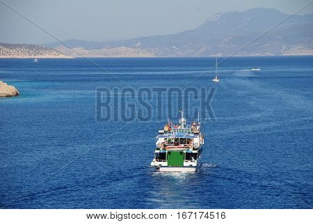 HALKI, GREECE - JULY 24, 2016: Boats departing the harbour at Emborio on the Greek island of Halki. One hour from Rhodes, the small Dodecanese island has a population of under 300 people.