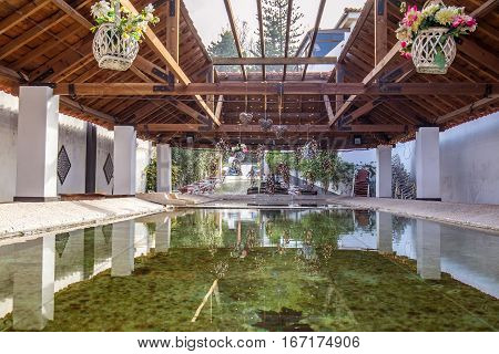 A zen garden inside a coffee shop that has a pool with fountain and many natural light coming from the ceiling
