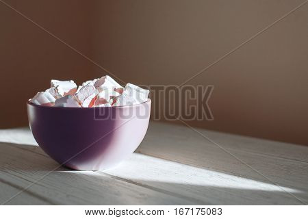 Marshmellow a purple wooden bowl on a white background. Top view. The concept of food.