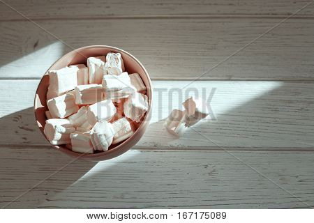 Marshmellow a wooden bowl on a white background. Top view. The concept of food.
