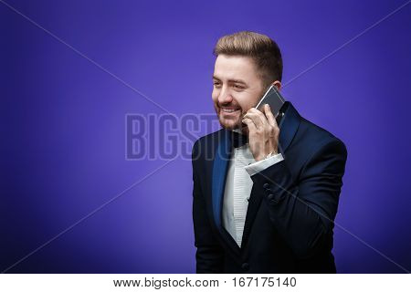 successful man in a tuxedo and bow tie talking on the phone. businessman holding a smartphone on blue background