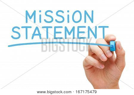 Hand writing Mission Statement with blue marker on transparent glass board.