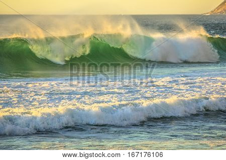 Big waves in Noordhoek Beach at sunset. Surfing in Cape Town, South Africa. Atlantic coast in Table Mountain National Park. Extreme sports leisure concept. Powerful waves background.