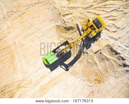 Aerial view of a excavator loading a truck in the mine or on construction site. Heavy industry from above. Industrial background with drone photography.