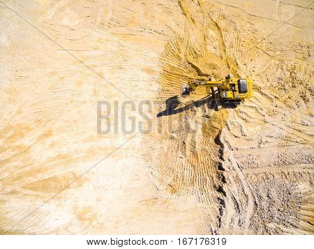 Aerial view of a working excavator in the mine. Industrial background on mining theme. Drone shot.