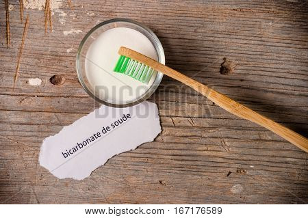 Baking Soda Next To A Tooth Brush On A Wooden Board.