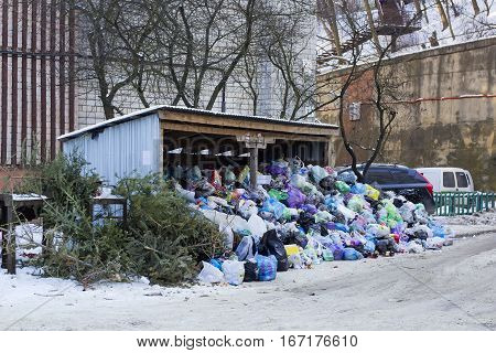 Metal hangar and garbage cans covered of large heap garbage on city street