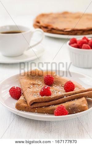 Healthy vegan carob crepes decorated with flaked coconut. Whole wheat chocolate crepes with fresh raspberries on white plate and a cup of tea and coffee on white wooden background. Healthy breakfast concept vertical