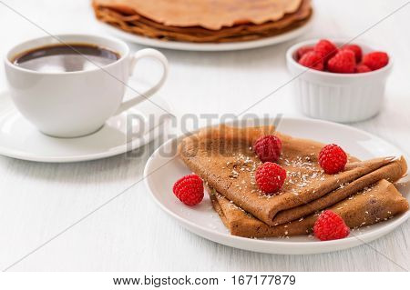 Healthy vegan carob crepes decorated with flaked coconut. Whole wheat chocolate crepes with fresh raspberries on white plate and cup of tea and coffee on white wooden background. Healthy breakfast concepthorizontal