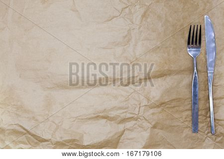 Wrapping paper and a fork and a knife. Is used to create a menu for a cafe . Good background to create restaurant menus, cafes bars.