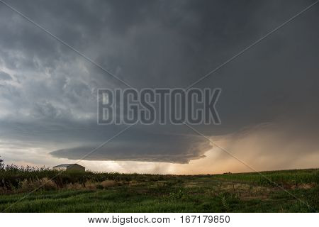 A picturesque supercell thunderstorm spins over the high plains of eastern Colorado, dropping hail and curtains of rain as it approaches.