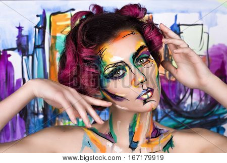 close-up fashion faceart portrait of young girl with art painting posing. Amazing creative picture with surrealistic face. Painted background