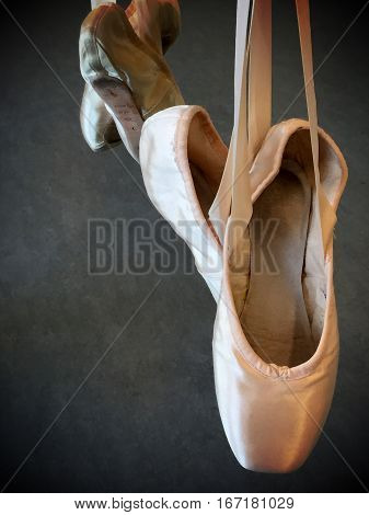 Pointe ballet shoes hanging up reflecting in a mirror with shallow depth of field and vignette. With space for text.