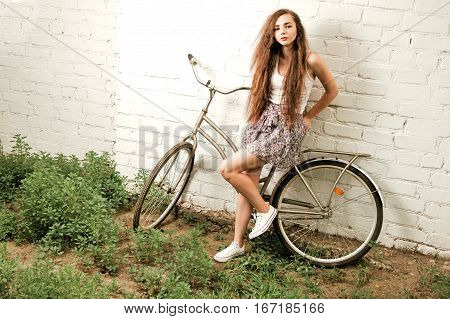 Pensive woman with city bike leaning back against white brick wall in summertime retro color shot, vintage looking image