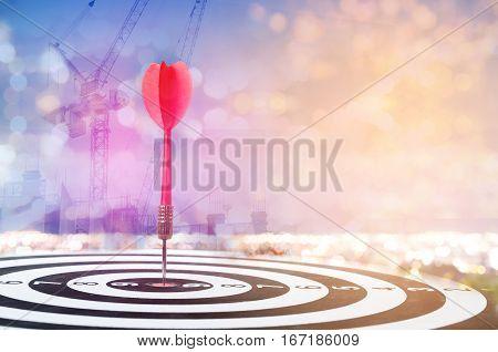 Close up shot red dart arrow on center of dartboard on bokeh blur background metaphor to target success construction concept