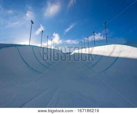 Empty winter snow halfpipe on a sunny day