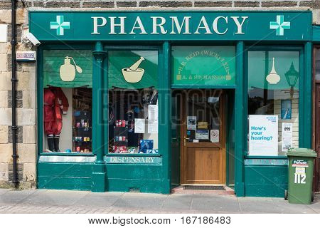 Wick Scotland - June 4 2012: Closeup of the green painted storefront of Wick Pharmacy owned by Mr. Manson. Display of colorful packages in windows. Trashcan upfront.